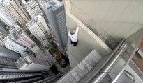 Cet homme joue avec sa vie en faisant des acrobaties du haut d'un gratte-ciel