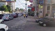 Des piétons grimpent sur la capot d'une voiture qui s'est arrêtée sur le passage pour piéton.
