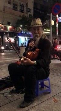 Nghệ sĩ đường phố Trí Hải biểu diễn đàn trên đường phố Sài Gòn