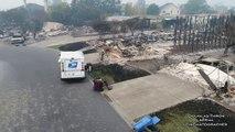 Un postier continue de livrer le courrier parmi les maisons brûlées