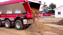 Dumper with a conveyor system for unloading without lifting the body