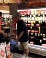 Un jeune ivre pense qu'il va pouvoir sortir avec ses paniers plein d'alcool sans payer