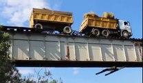 Ce camion roule sur un pont... ferroviaire sur les rails du train en équilibre !