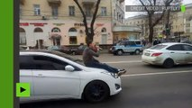 Russie : un homme déguste une bière… sur le capot d'une voiture