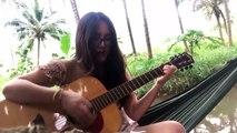 Une fille casse une corde en jouant de la guitare au bord d'une rivière