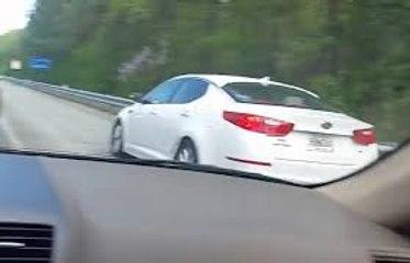 Un automobiliste remonte les bouchons sur l'autoroute en passant sur la bande d'arrêt d'urgence