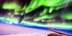 Un pilote davion vole à travers des aurores boréales
