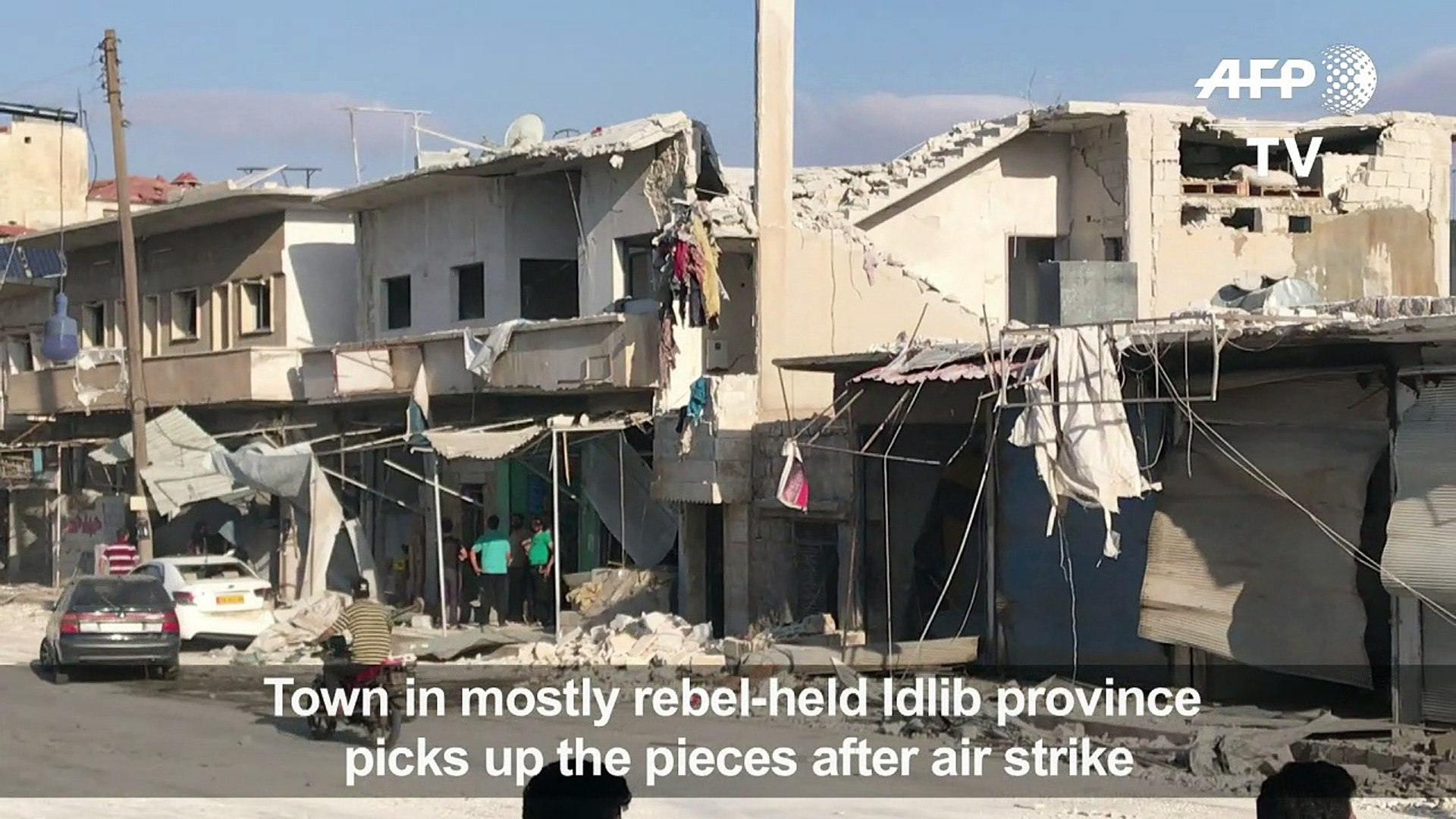 Syrians clear up the aftermath following air strikes on Binnish