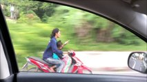 Cette femme en mobylette envoie un texto à deux mains avec son fils assis devant elle