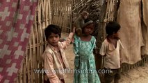 Little Assamese girl with macaque monkey sitting on her shoulder