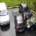 Un grand père pousse sa voiture pour sortir d'une place de parking