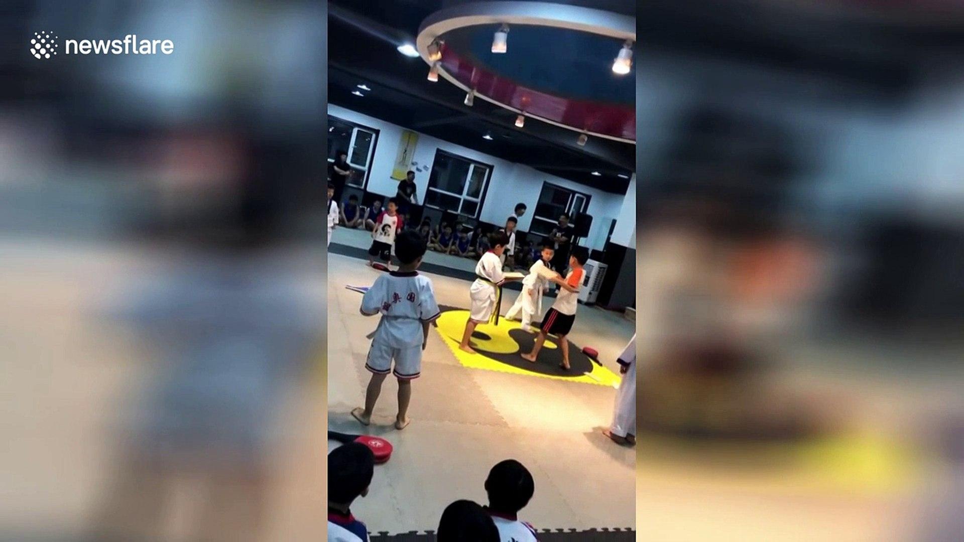 Boy helps friend break planks after his roundhouse kick fails