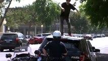 Un homme saute sur une voiture de police pour la détruire et se fait arreter