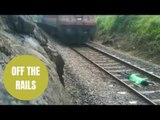 Man lays down on a railway track while a train speeds over him