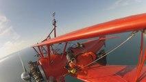 Im Doppeldecker: Frau steigt auf Flugzeugflügel