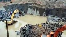 Un ouvrier provoque une explosion d'eau en faisant tomber une énorme pierre.