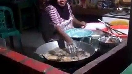 Une thaïlandaise  plonge ses mains dans l'huile bouillante