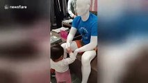 Adorable moment polite toddler greets mannequins inside shopping mall