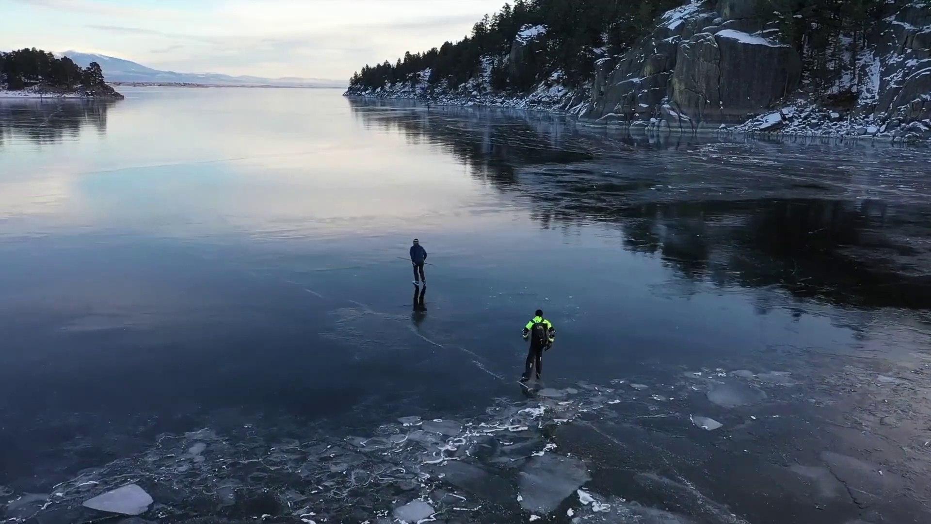 Ils font du patin à glace sur un lac gelé transparent - Canyon Ferry Lake