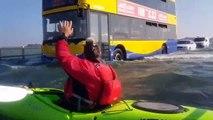 Faire du kayak sur une route inondée alors que des voitures roulent encore