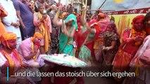 Frauen verdreschen Männer in Indien mit Stöcken