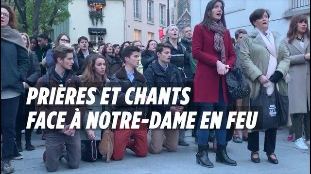 Des croyants à genoux chantent face à Notre-Dame en feu