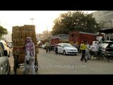 Fruits and veggies stacked up on tri-cycle goods carriers in the Azadpur mandi
