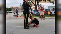 11-year-old boy ties officer's shoelaces during Fourth of July parade
