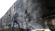 Palestinian artist: Israel's separation wall scary racist symbol