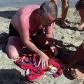 Sauvetage d'une mouette par des touristes sur la plage, prisonnière d'une ligne de pêche