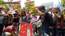 Protesters burn a Chinese flag in a rally outside the Chinese Consulate in Makati