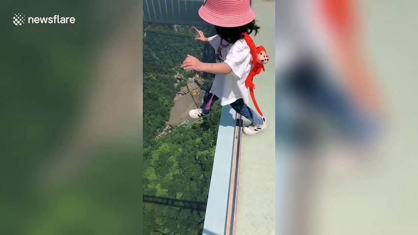 Don't look down! Fearless girl steps onto 260-metre-high glass walkway in China's Zhangjiajie