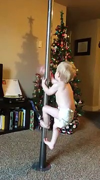 toddler climbs up dancing pole in the living room