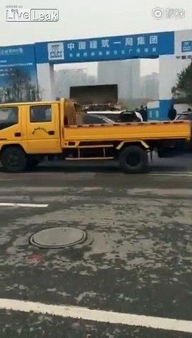 Un ouvrier en colère pousse des voitures mal garées avec sa pelleteuse