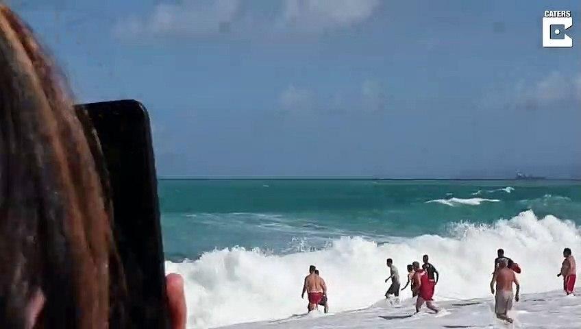 Un sauveteur intervient pour sortir un enfant piégé dans des vagues énormes