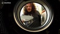 Man loads washing machine with dirty dishes