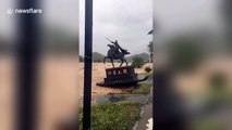 A statue in China is washed away by typhoon Lekima