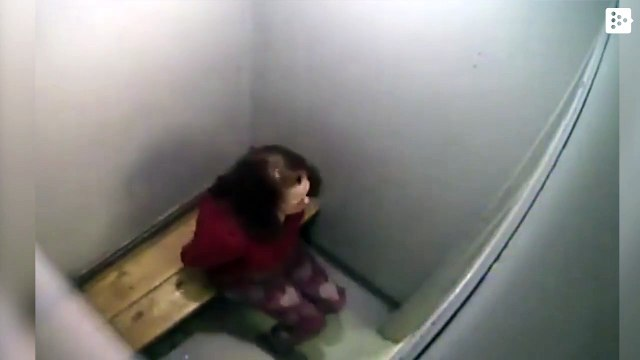A US policeman hits a woman in handcuffs for kicking her cell door