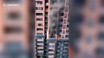 Cet homme s'échappe d'un incendie en escaladant l'immeuble son fils sur le dos