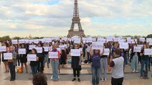People write the names of women killed during a rally in Paris