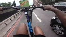Des jeunes à vélo roulent en wheeling sur la route et l'un d'entre eux percute une voiture