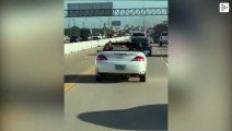 A man takes advantage of the traffic to do weights while driving his convertible