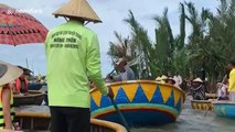 Vietnamese man rapidly spins rowing boat in circular motion while on river