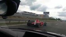 Un automobiliste se fait doubler par une Formule 1 sur l'autoroute
