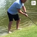 This golfer falls to the lake when trying to get out a complicated ball