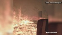 Firetruck drives through road surrounded by raging wildfire