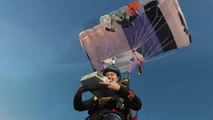Two Skydivers Eat Pizza While Floating in Air Under Parachutes
