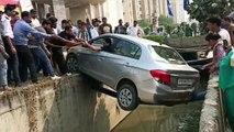 Une voiture en équilibre sur un tuyau étroit surplombant un fossé