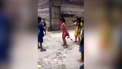 Niños saltan usando una enorme serpiente muerta