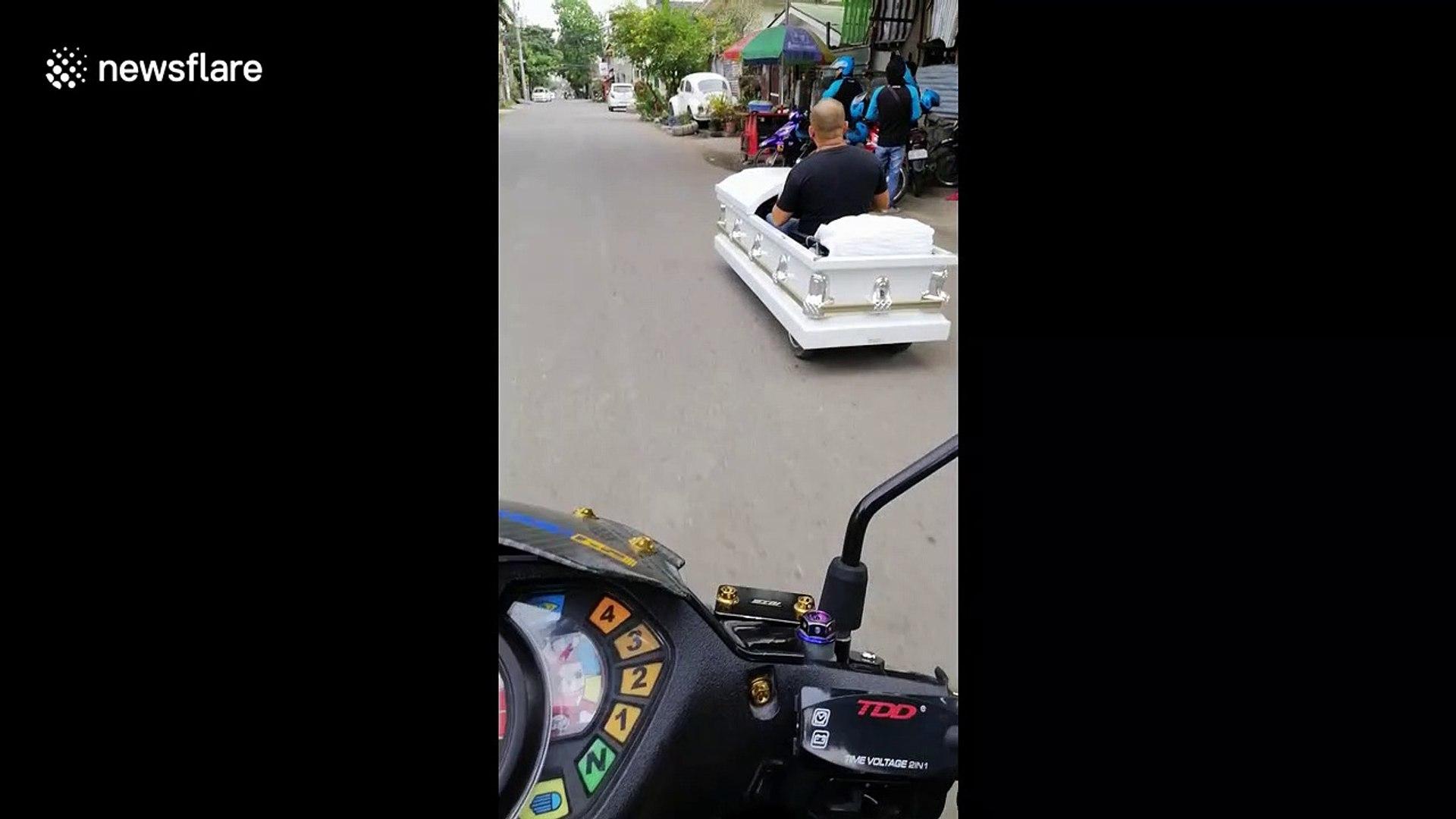 Bizarre moment Filipino motorist drives along road in 'coffin-mobile'